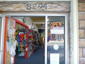 Looking in the door of Trailside bike at bike flags and accessories.