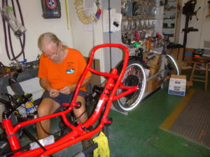 Gary is working on a red Catrike Trail without a seat on it. It has a bionx black disc on the hub of the back wheel.